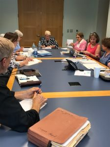 League members sitting at table during monthly board meeting